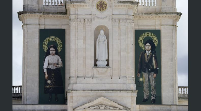 The pictures of Jacinta, left, and Francisco Marto, hang on the facade of the Sanctuary of Our Lady of Fatima, Saturday, May 13, 2017, in Fatima, Portugal. Pope Francis urged Catholics on Friday to